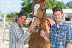 Woman and man standing beside horse Royalty Free Stock Image