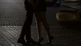 Woman and man standing in night street, holding hands, kissing, legs in shot
