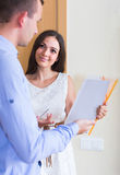 Woman and man standing with official papers near door Royalty Free Stock Photo