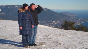 Woman and man standing on the snow-covered plateau. Below can be seen the city and the sea stock footage