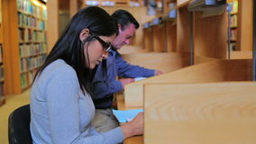 Woman and man studying. In library stock footage