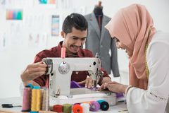 Woman and man tailor using sewing machine. Man and women tailor or fashion designer using sewing machine in his office Stock Image