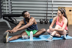Woman and man talking and stretching on sport towel Royalty Free Stock Image