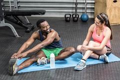 Woman and man talking and stretching on sport towel Stock Images