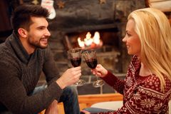 Woman and man toasting delicious red wine at romantic fireplace Stock Photo