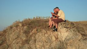 Woman and man on the top of a mountain in the sunset stock video footage