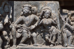 Woman and man in traditional style dancing on relief of the 12th century Hoysaleshwara temple in Halebidu, India. Stock Image