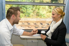 Woman and man on train holding hands Royalty Free Stock Photo