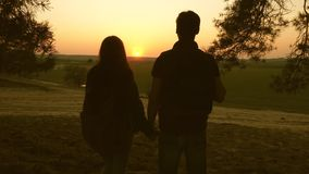A woman and a man travel, walk in forest, hug and enjoy the scenery at sunset. Lovers travelers travel with backpacks stock video footage
