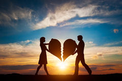 Woman and man with two halves of broken heart going to be joined in one. Love. Woman and man holding two halves of broken heart going to be joined in one. Love Stock Photography