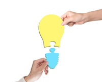 Woman and man two hands assembling one bulb shape puzzle Royalty Free Stock Photos