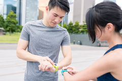 Woman and man using smart watch and get running together Stock Images