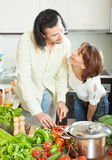 A woman and a man with vegetables in the kitchen Royalty Free Stock Photography