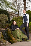 Woman and man in Victorian fashion near waterfall in park Stock Images