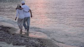 Woman and man walking on the beach stock video footage