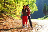 Woman and man walking cross country trail in autumn forest Stock Photos