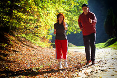 Woman and man walking cross country trail in autumn forest Stock Image