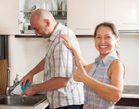 Woman and man washing dishes Stock Photography