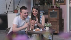 A woman in a man watching photos on a smartphone a summer cafe stock footage