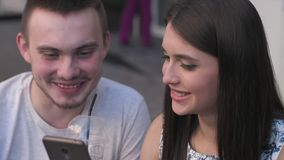 A woman in a man watching photos on a smartphone a summer cafe stock video footage