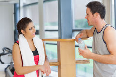 Woman and man with water bottle chatting at gym Stock Photos