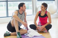 Woman and man with water bottles chatting at gym Stock Photography
