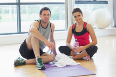 Woman and man with water bottles sitting at gym Royalty Free Stock Photography
