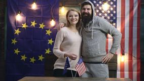 Woman and a man are welcomed against the backdrop of European and American flags. Handshake over American and EU flags. Concept of friendship between American stock video footage