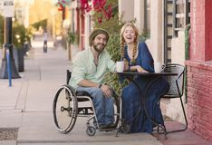 Woman with Man in Wheelchair at Cafe Table. Woman having coffee with friend in wheelchair on sidewalk Royalty Free Stock Photos