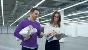 Woman and man work with engineering blueprint and papers, walking in a room. stock footage