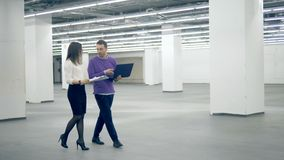 Woman and man work with a laptop while walking in a commercial area, professional engineers. Woman and man work with a laptop while walking, professional stock video footage