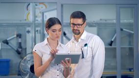 A woman shows a man information on a tablet. stock footage