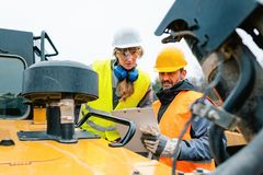 Woman and man worker in quarry on excavation machine stock photos