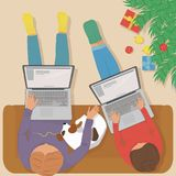 Woman and man working on laptop at home at the Christmas tree. Woman and man working on laptop at home, sitting on a comfortable sofa with the dog. Standing Royalty Free Stock Photos