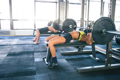 Woman and man workout with barbell on bench Stock Photography