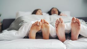 Woman and man couple lying in bed together sleeping under blanket, focus on feet. Woman and man young couple are lying in bed together sleeping under white stock video footage