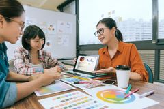 Woman manager using mobile digital tablet pad. Smiling pretty women manager using mobile digital tablet pad showing design planning for her designer colleagues Stock Image