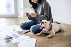 Woman managing the debt sitting with pet dog Royalty Free Stock Photo