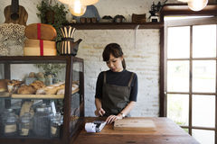 Woman managing a small bakery house. Asian Woman managing a small bakery house Royalty Free Stock Photo