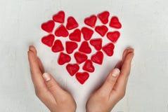Woman& x27; mani di s con cuore fatto dalla gelatina di frutta Immagine Stock