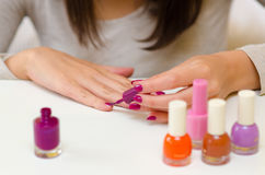Woman manicure nail paint purple color on white table at home Stock Photography