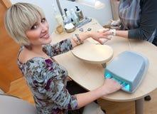 Woman in manicure salon stock image