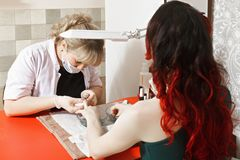 Woman in manicure salon. Sitting against manicurist at the red desk. Horizontal shot Royalty Free Stock Photography