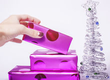Woman manicured hand puting christmas gift to rest Stock Images