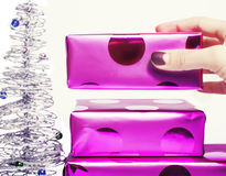 Woman manicured hand puting christmas gift to rest Stock Photo