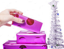 Woman manicured hand puting christmas gift to rest pile of purple gifts close up isolated silver little tree Stock Image