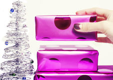 Woman manicured hand puting christmas gift to rest pile of purple gifts close up silver little tree cute stock photography
