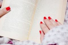 Woman manicured hand with red nails and book. Woman manicured hand with red nails read the book wrapped in a blanket Royalty Free Stock Photo