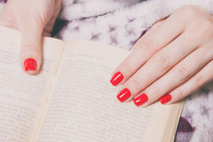 Woman manicured hand with red nails and book royalty free stock photos