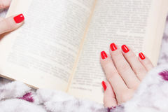 Woman manicured hand with red nails and book stock photography